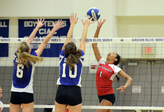 Greenwich's Jenny Cespedes (1) pops the ball over the net as Darien's Kelly Kosnik (6) and Taylor Cockerill (10) defend during the girls volleyball match at Darien High School on Tuesday, Nov. 13, 2012. Photo: Amy Mortensen / Connecticut Post Freelance