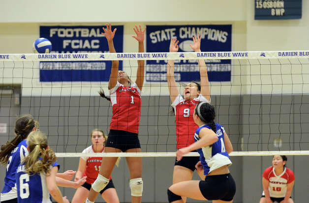 Darien's Lauren Pryor (4) gets a shot past Greenwich's Jenny Cespedes (1) and Mirei Kato (9) during the girls volleyball match at Darien High School on Tuesday, Nov. 13, 2012. Photo: Amy Mortensen / Connecticut Post Freelance