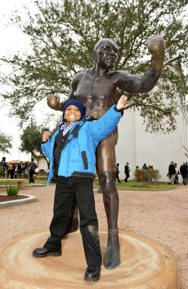 Daniel Speights, 6, of Missouri City, poses for a picture with a new statue of Jack Johnson after a dedication ceremony for Jack Johnson Park at the Old Central High School, Tuesday, in Galveston. Johnson was the first African American heavyweight champion. Photo: Nick De La Torre, Houston Chronicle / © 2012  Houston Chronicle