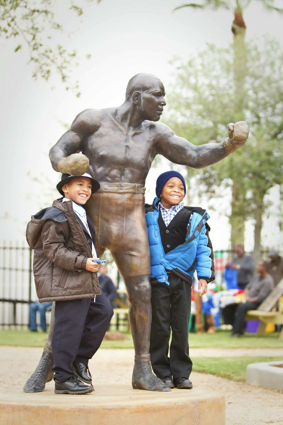 Jedadiah Baker, of Austin, left, and his cousin Daniel Speights, of Missouri City, poses for a picture with a new statue of Jack Johnson after a dedication ceremony for Jack Johnson Park at the Old Central High School, Tuesday, in Galveston. Johnson was the first African American heavyweight champion.
