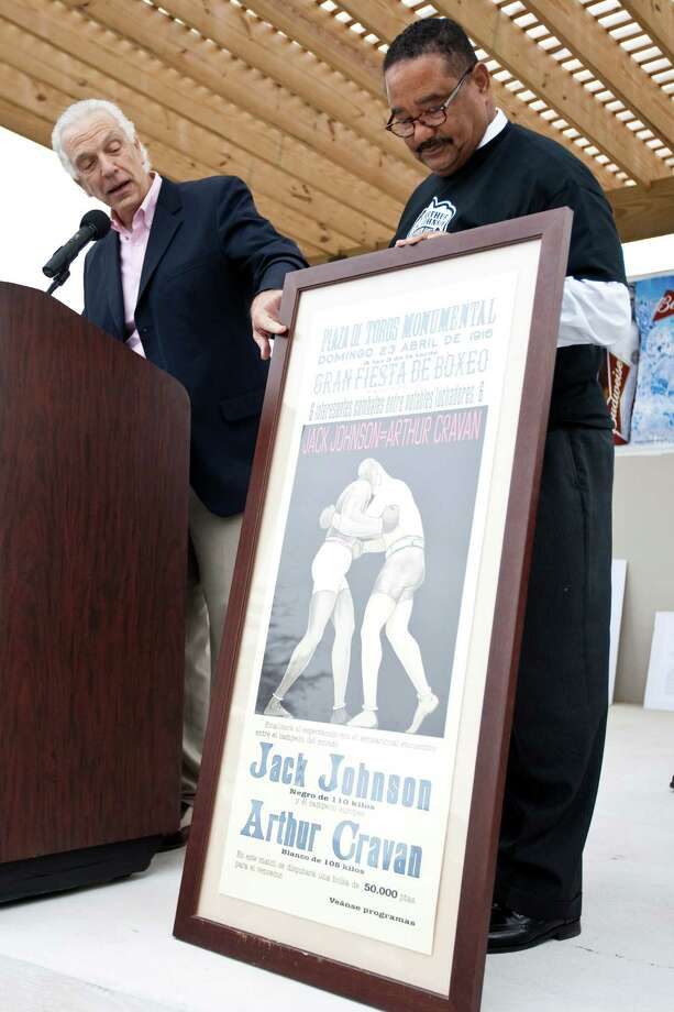 Paulie Gaido, left, presents Douglas Matthews with a vintage Jack Johnson fight poster during a dedication ceremony for Jack Johnson Park at the Old Central High School, Tuesday, in Galveston. Matthews is on the board of the culture center and part coordinator of the park. Johnson was the first African American heavyweight champion. Photo: Nick De La Torre, Houston Chronicle / © 2012  Houston Chronicle