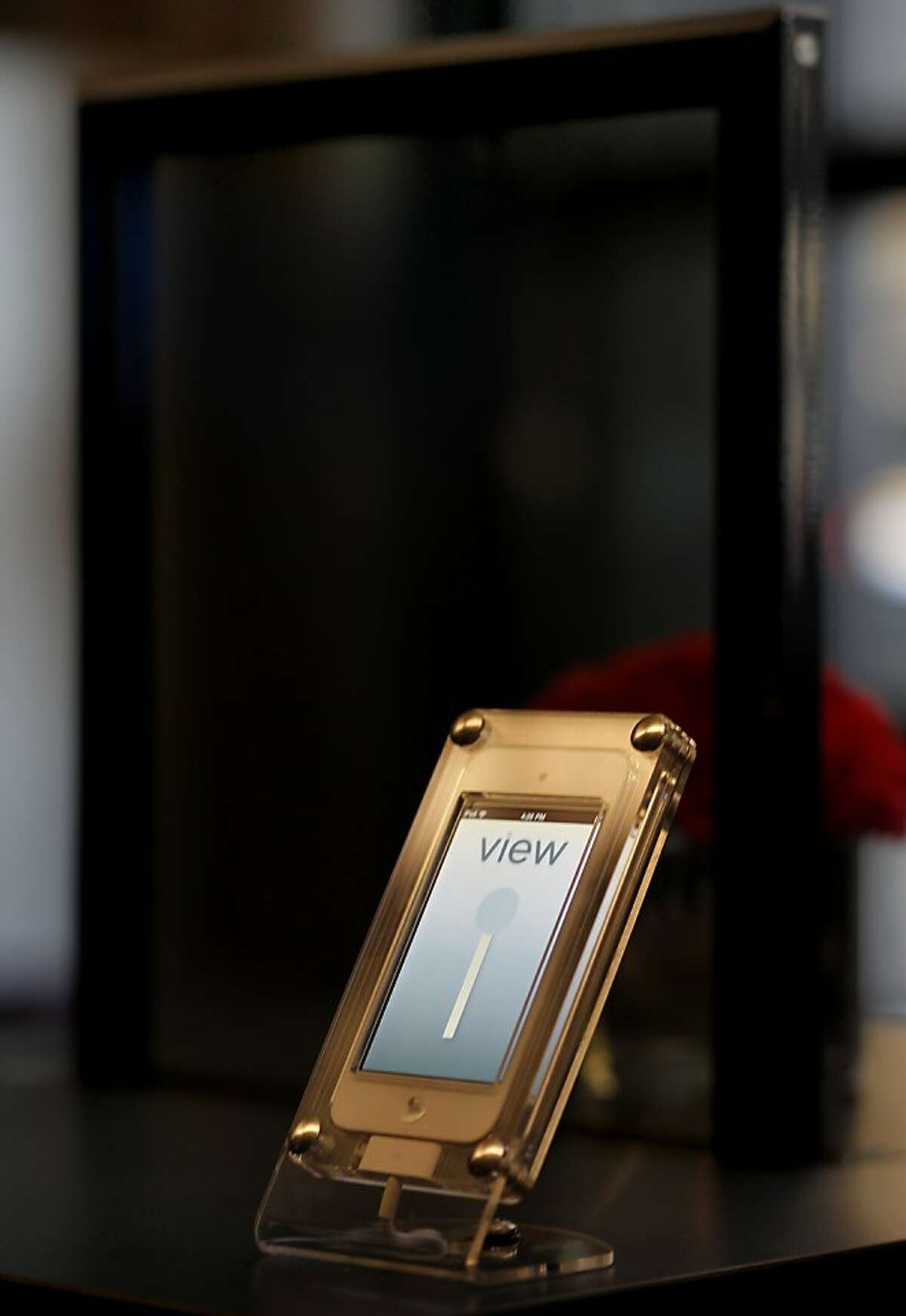 A display at the W Hotel in San Francisco, Calif. shows the phone application that can be used to darken glass, a sample which is in the rear. Milpitas, Calif. technology firm View Inc. has replaced windows at the W Hotel with their own