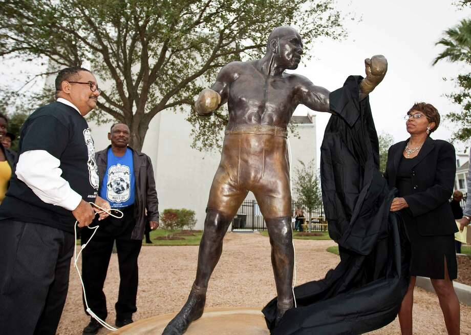 "Adrienne Ison, an sculptress from Austin, unveils a statue she made of Jack Johnson during a dedication ceremony for Jack Johnson Park at the Old Central High School, Tuesday, Nov. 13, 2012, in Galveston. Johnson was the first African American heavyweight champion December 26, 1908. Johnson was known for constantly disregarding the social and economic ""place"" of African Americans in society. ( Nick de la Torre / Houston Chronicle ) Photo: Nick De La Torre, Staff / © 2012  Houston Chronicle"