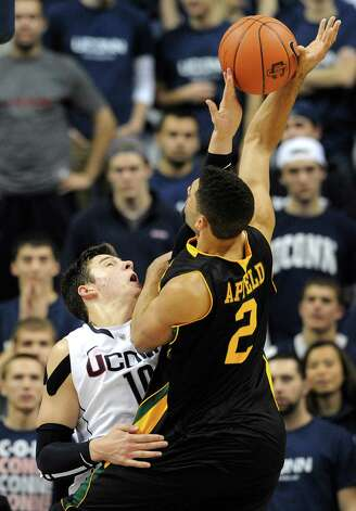 Connecticut's Tyler Olander, left, blocks a shot by Vermont's Luke Apfeld in the second half of an NCAA basketball game in Storrs, Conn., Tuesday, Nov. 13, 2012. No. 23 Connecticut won 67-49. Apfeld let Vermont with nine points. Olander had nine points and nine rebounds. (AP Photo/Jessica Hill) Photo: Jessica Hill, Associated Press / FR125654 AP