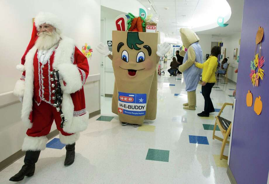 Santa Claus along with H-E-B Buddy and Ikea's Fabler Bjorn walk the hallways as they visit patients during a mini holiday parade at Texas Children's Hospital on Tuesday, Nov. 13, 2012, in Houston. Photo: J. Patric Schneider, For The Chronicle / © 2012 Houston Chronicle