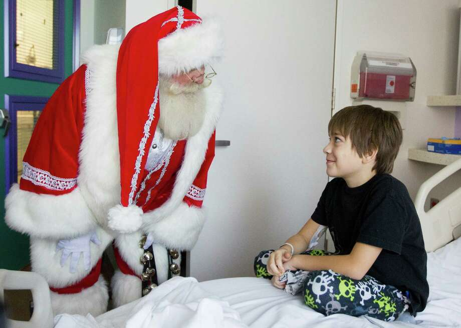 Santa Claus visits with Adrian Garcia, 9, in his hospital room during a mini holiday parade through the hallways of Texas Children's Hospital on Tuesday, Nov. 13, 2012, in Houston. Photo: J. Patric Schneider, For The Chronicle / © 2012 Houston Chronicle