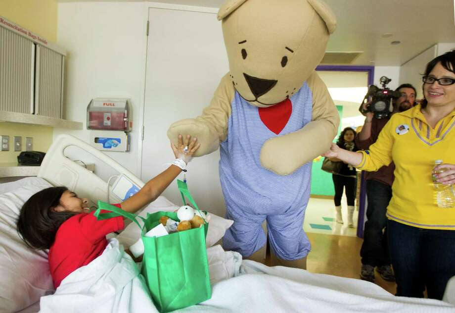 Ikea's Fabler Bjorn visits with Karla Burden, 11, in her hospital room during a mini holiday parade through the hallways of Texas Children's Hospital on Tuesday, Nov. 13, 2012, in Houston. The characters along with Santa Claus also brought gifts to the patients. Photo: J. Patric Schneider, For The Chronicle / © 2012 Houston Chronicle