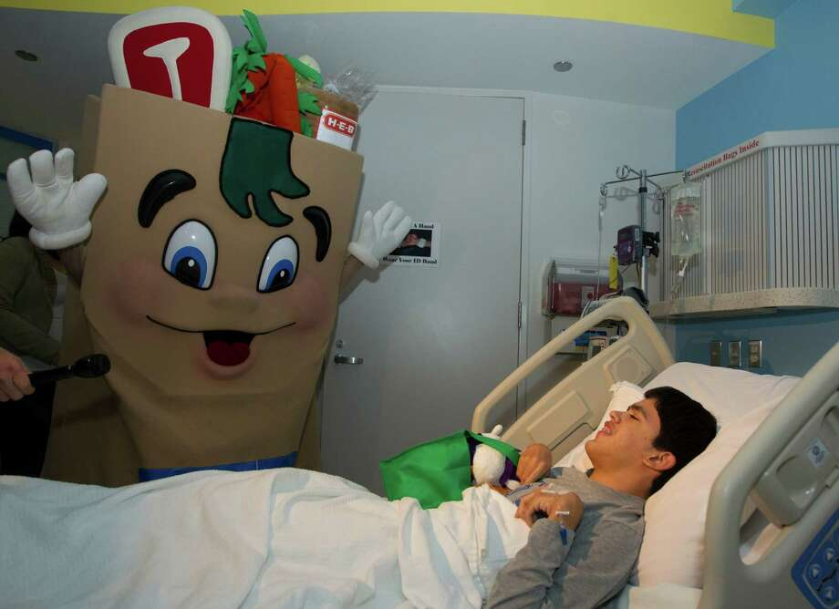 H-E-B Buddy visits with Oswaldo Guzman, 16, in his hospital room during a mini holiday parade through the hallways of Texas Children's Hospital on Tuesday, Nov. 13, 2012, in Houston. The characters along with Santa Claus also brought gifts to the patients. Photo: J. Patric Schneider, For The Chronicle / © 2012 Houston Chronicle