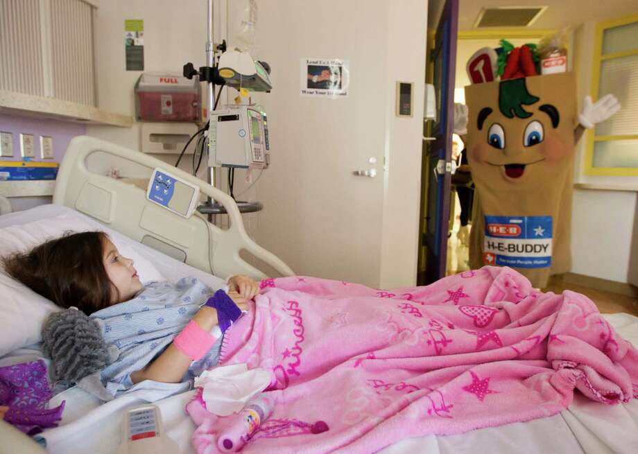 H-E-B Buddy visits with Abigail Green, 6, in her hospital room during a mini holiday parade through the hallways of Texas Children's Hospital on Tuesday, Nov. 13, 2012, in Houston. The characters along with Santa Claus also brought gifts to the patients. Photo: J. Patric Schneider, For The Chronicle / © 2012 Houston Chronicle