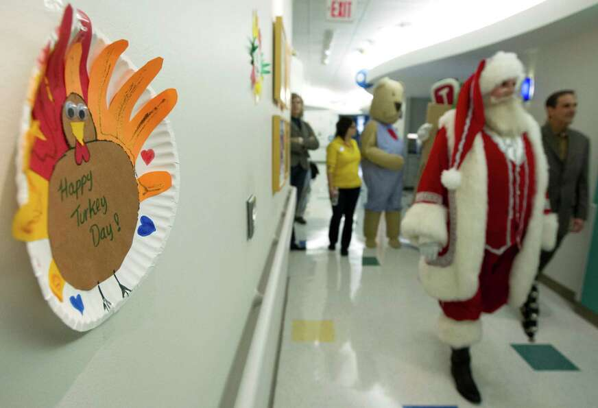 Santa Claus along with several characters walk the hallways as they visit patients during a mini hol