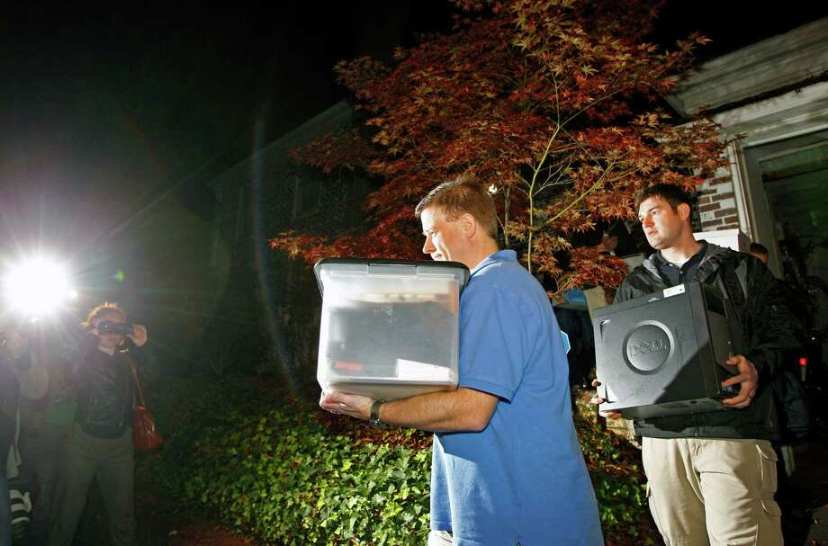 FBI agents carry boxes and a computer from the Charlotte, N.C., home of Paula Broadwell, the woman whose affair with retired Gen. David Petraeus led to his resignation as CIA director. Photo: Chuck Burton, STF / AP
