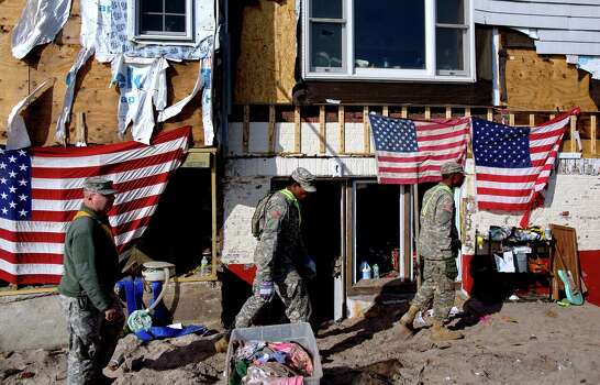 Members of the 69th Infantry Army National Guard get ready to work at the storm damaged home of Howard Schneider in the Belle Harbor neighborhood of the borough of Queens, New York, Monday, Nov.12, 2012, in the wake of Superstorm Sandy. Worn flags that hang on the house, once flew at the nearby beach and were found in the cleanup. Photo: Craig Ruttle, Associated Press / FR61802 AP
