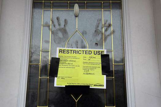 Muddy handprints mark the front door of a home that was heavily damaged by Superstorm Sandy on November 13, 2012 in New York City. More than two weeks after the devastating storm, Staten Island continues to recover. Photo: John Moore, Getty Images / 2012 Getty Images