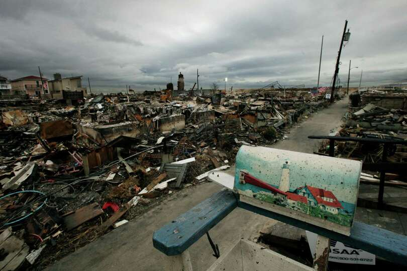 A mailbox with a lighthouse design sits on the porch of a burned out home in the Breezy Point sectio