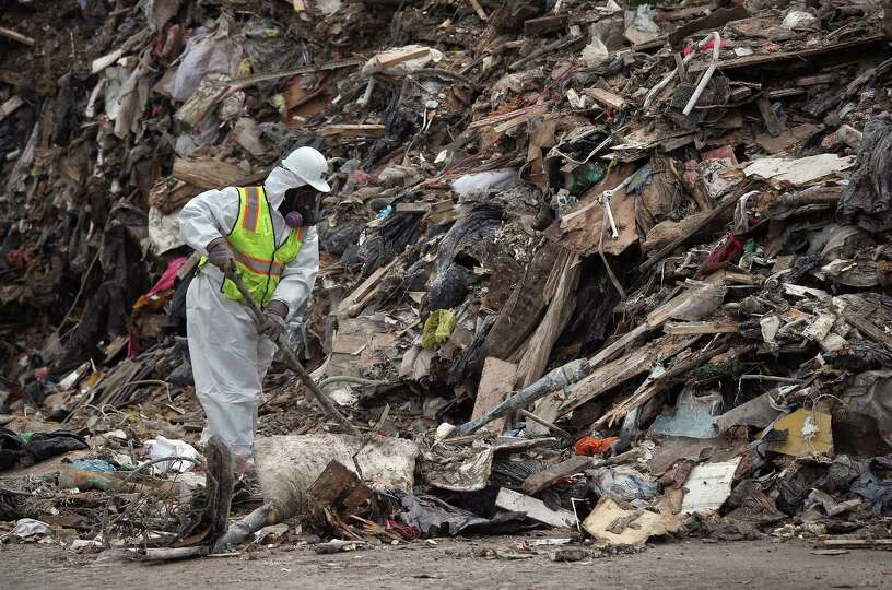 A disaster cleanup worker looks for environmentally dangerous waste at a mass dump of household poss