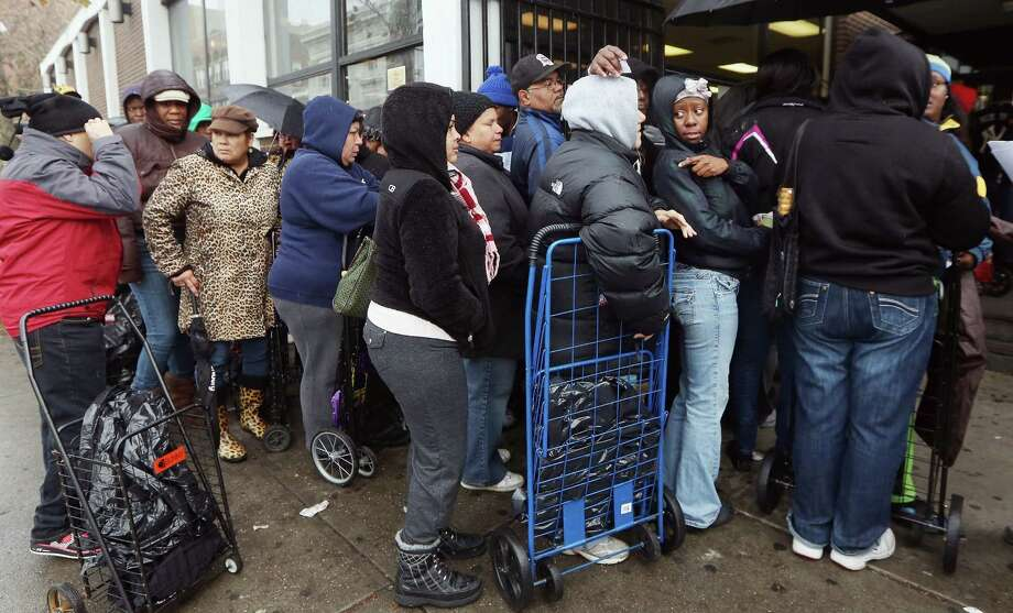 People wait on line to receive some of the 1,500 donated coats from New York Cares in the Far Rockaway neighborhood on November 13, 2012 in the Queens borough of New York City. New York Cares started their annual coat drive early this year in order to assist those affected by Superstorm Sandy. They hope to collect 200,000 coats this winter. Photo: Mario Tama, Getty Images / 2012 Getty Images