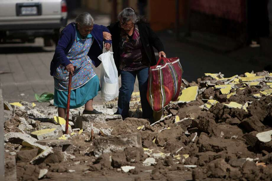 Women help each other walk over the rubble from buildings that fell during the earthquake in San Pedro, Guatemala, Monday, Nov. 12  2012. Authorities in Guatemala have lowered the death toll from last week's 7.4-magnitude earthquake to 42 from 52, after some people who had been reported dead were found alive. Photo: Moises Castillo, Associated Press / AP