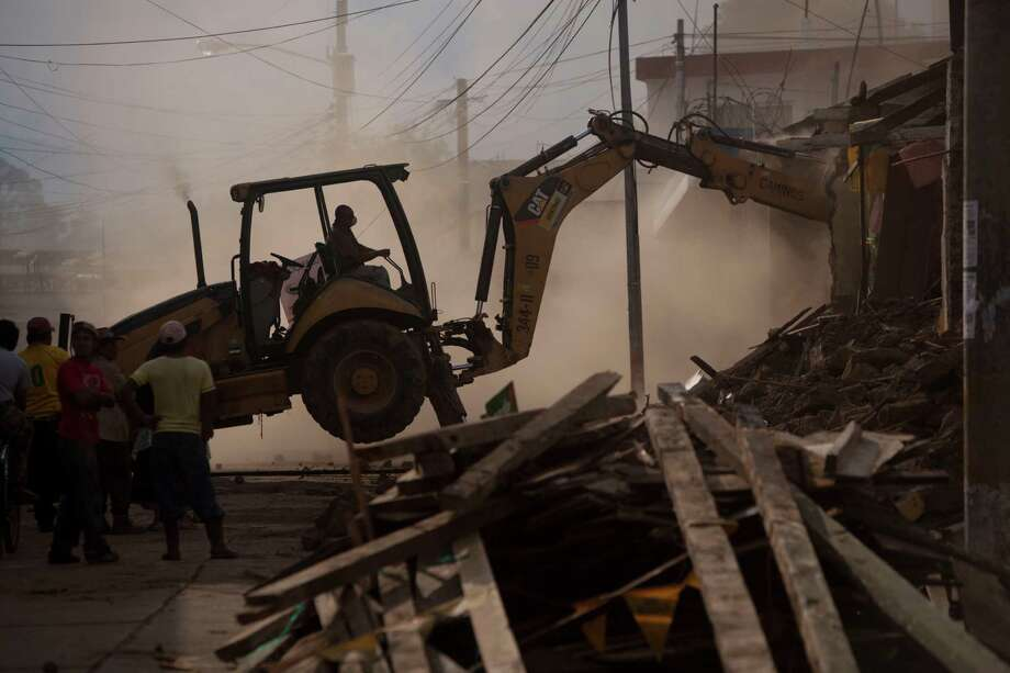 Workers use heavy machinery to demolish buildings damaged by an earthquake in San Marcos, Guatemala, Monday, Nov. 12, 2012. Authorities in Guatemala have lowered the death toll from last week's 7.4-magnitude earthquake to 42 from 52, after some people who had been reported dead were found alive. Photo: Moises Castillo, Associated Press / AP