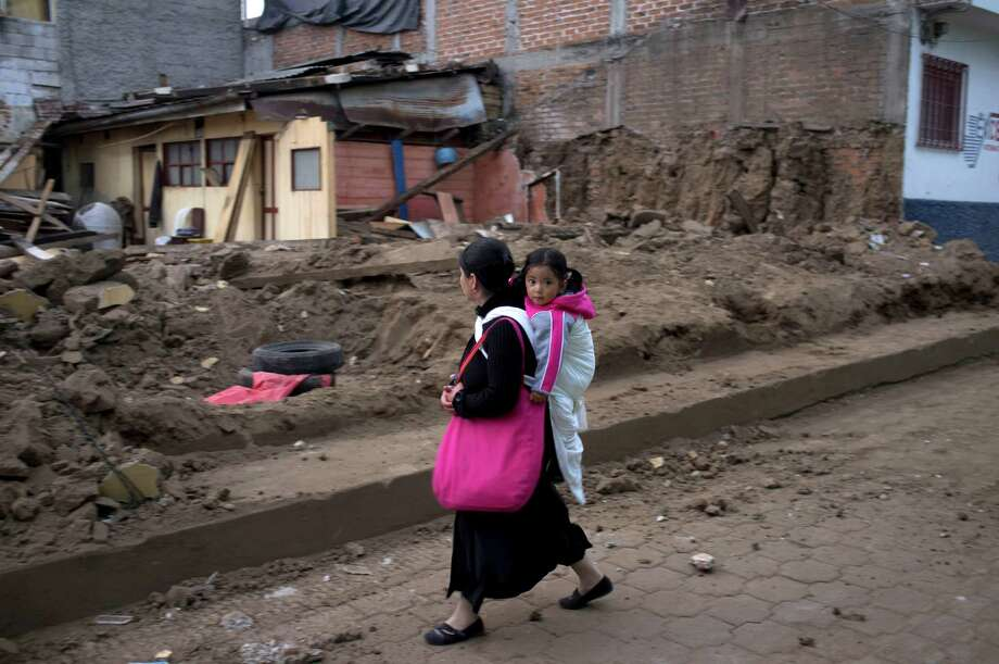 A resident carrying a girl walks past a home damaged by an earthquake in San Pedro, Guatemala, Monday, Nov. 12, 2012. Authorities in Guatemala have lowered the death toll from last week's 7.4-magnitude earthquake to 42 from 52, after some people who had been reported dead were found alive. Photo: Moises Castillo, Associated Press / AP