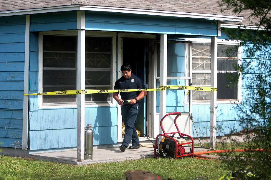 A firefighter investigates at the home where an elderly woman was pulled from a blaze. She later died. Photo: Cody Duty, Staff / © 2012 Houston Chronicle