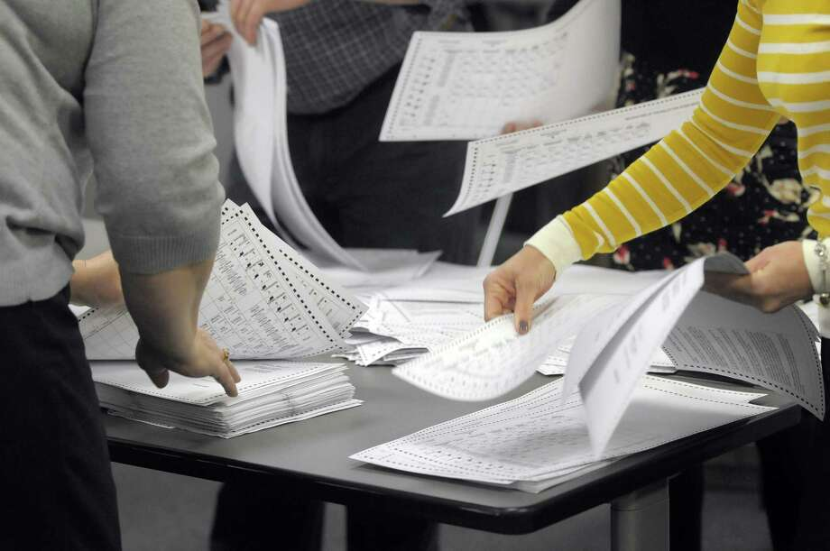 Employees of the Albany County Board of Elections go through paper ballots from the voting machines as they performed a 3% audit of the voting machines on Tuesday, Nov. 13, 2012 in Albany, NY.  The ballots they were counting come from an election district in the 46th State Senate District.  The employees were counting to verify that the number of paper ballots matched the number of ballots the machine registered as having been cast.  (Paul Buckowski / Times Union) Photo: Paul Buckowski  / 00020021A