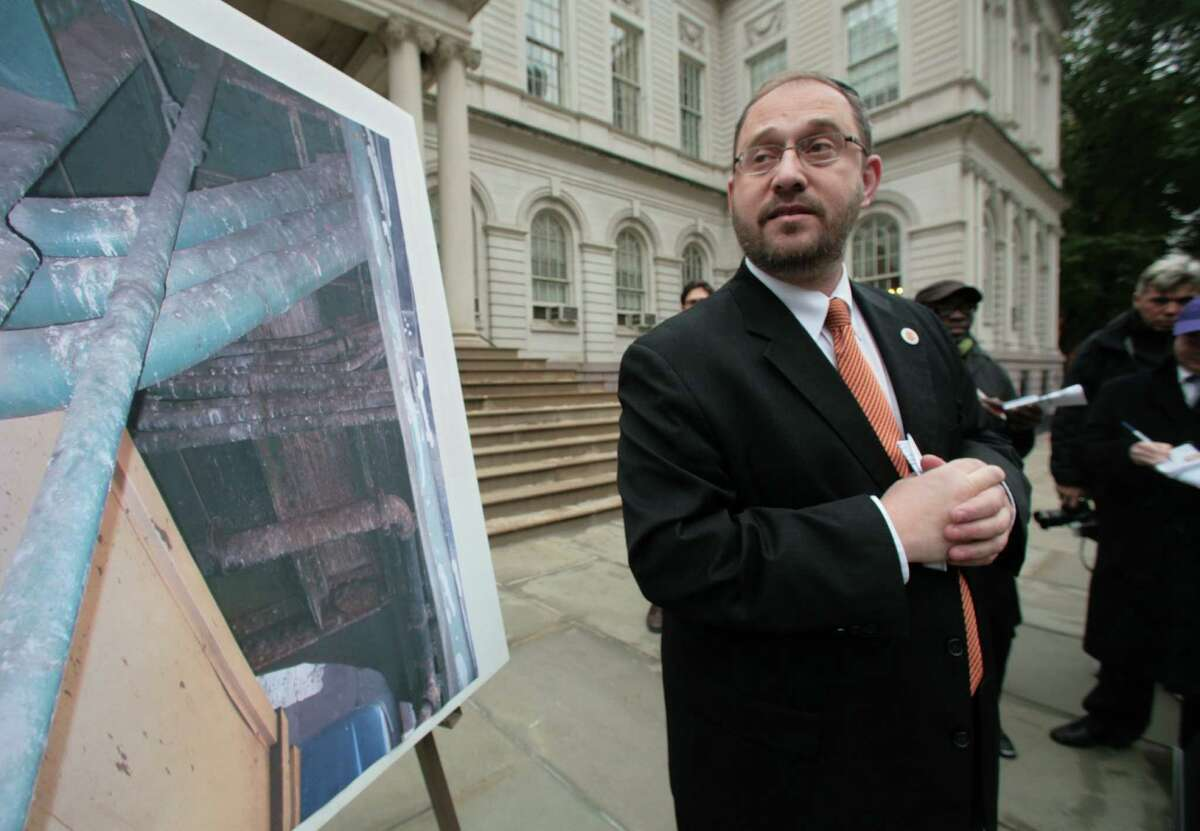 Standing next to photo of pipes covered with pigeon mess, Council Member Simcha Felder holds a press conference , Monday Nov. 12 , 2007, announcing legislation to ban feeding pigeons, City Hall, New York. (AP Photo/Bebeto Matthews)