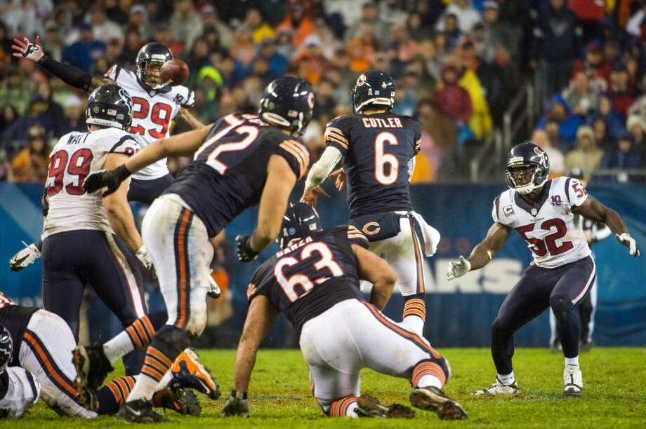 Bears quarterback Jay Cutler (6) gets away a pass as Texans strong safety Glover Quin (29) leaps to defend and inside linebacker Tim Dobbins (52) closes in during the second quarter. Cutler was hit hard by Dobbins after he released the ball, causing a concussion on the play.  Dobbins was penalized for the hit, offsetting a penalty against Cutler for an illegal forward pass.  Cutler finished the half, but did not return after halftime. (Houston Chronicle)