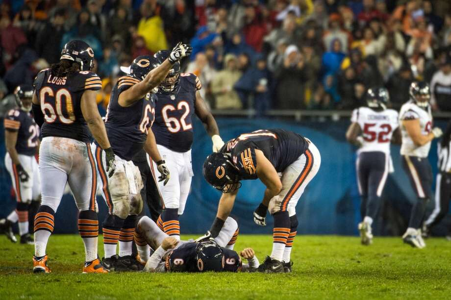 Bears center Roberto Garza (63) and tackle Gabe Carimi (72) rush to the aid of quarterback Jay Cutler (6) after he was hit by Texans inside linebacker Tim Dobbins (52) after throwing a pass during the second quarter. (Houston Chronicle)