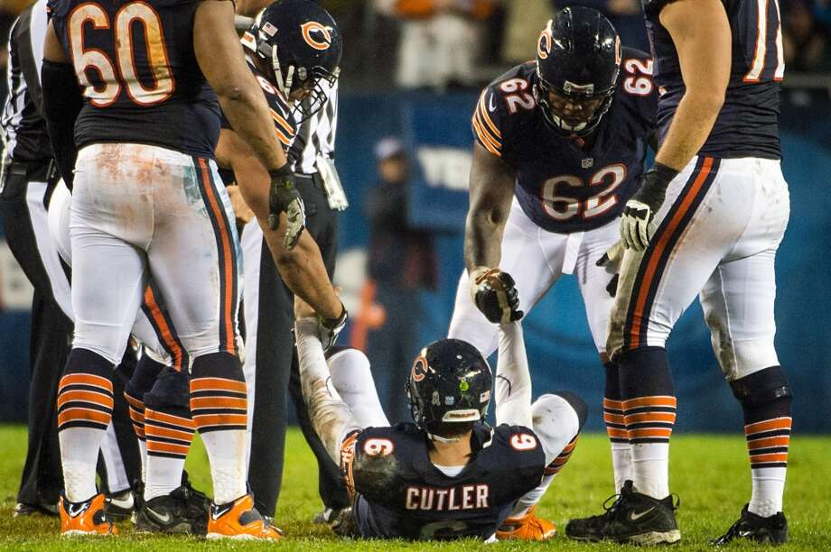 Jay Cutler is helped to his feet after he was hit by Texans linebacker Tim Dobbins after throwing a pass during the second quarter. (Houston Chronicle)