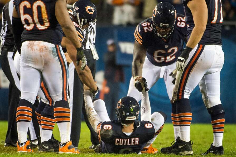 Jay Cutler is helped to his feet after he was hit by Texans linebacker Tim Dobbins after throwing a