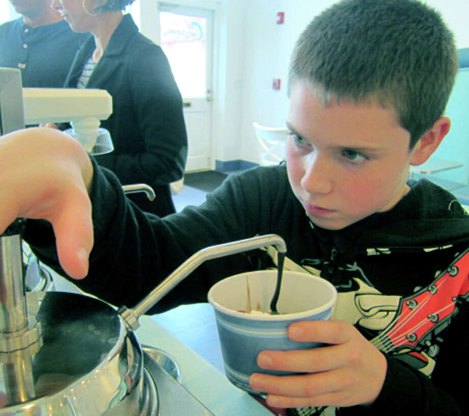 The focus of Zachary Walitynski of New Milford is entirely on the task at hand as he applies just the right amount of hot fudge to his yogurt at Tasty Waves, along the Village Green in New Milford. Nov. 11, 2012 Photo: Norm Cummings