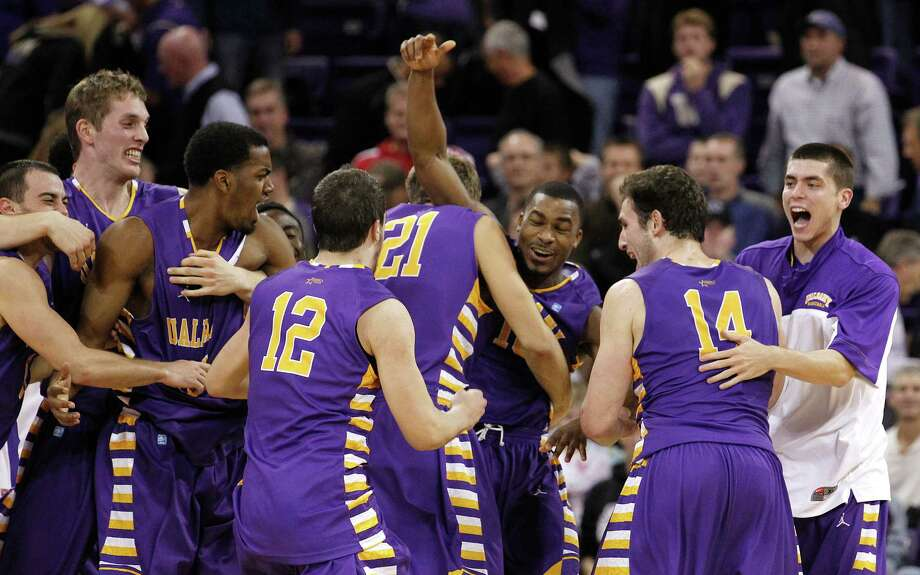 Albany's Mike Black, center, raises his arms as he celebrates with teammates after they defeated Washington in an NCAA college basketball game, Tuesday, Nov. 13, 2012, in Seattle. Black hit the winning shot as Albany won 63-62. (AP Photo/Elaine Thompson) Photo: Elaine Thompson