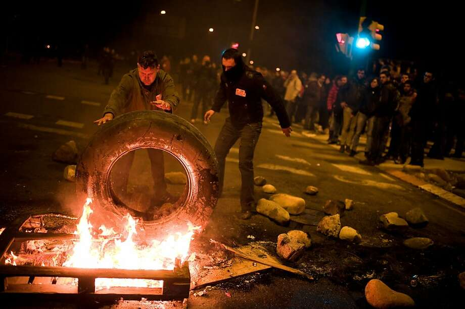 Demonstrators set up a barricade of burning tires at the main entrance of Mercabarna, the biggest wholesale market in the city, at the beginning of a 24-hour strike on November 14, 2012 in Barcelona, Spain. Spain's trade unions have called for today a general strike, the second of Mariano Rajoy's presidency. Protestors from social movements are expected to join striking public sector workers to demonstrate against austerity cuts, labour reforms and an unemployment rate of 25 percent. Photo: David Ramos, Getty Images