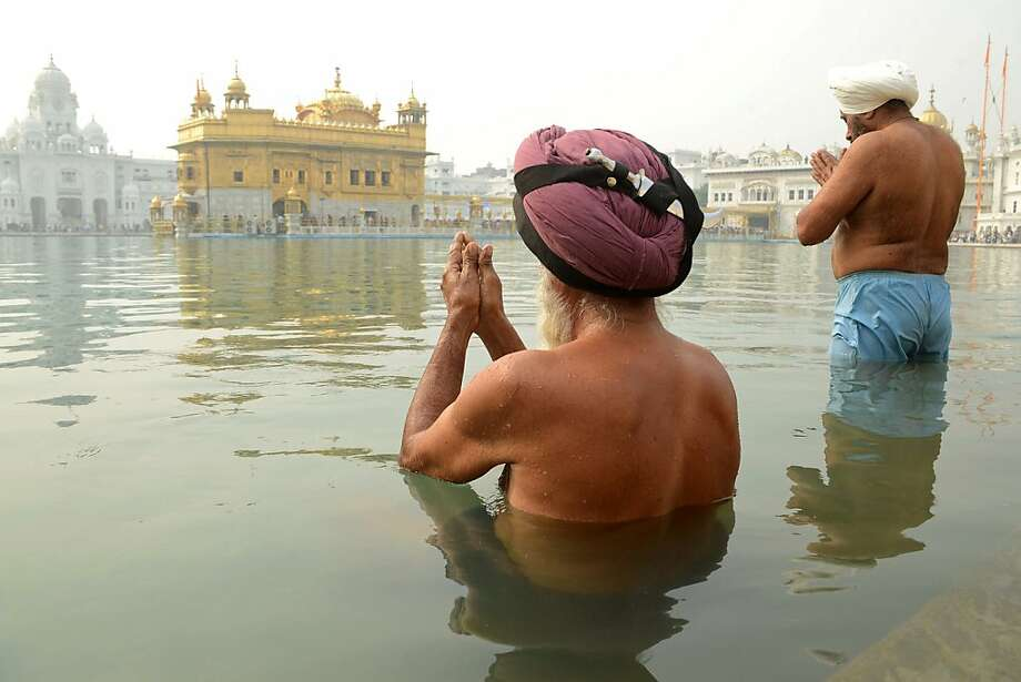 Soaking Sikhs:Sikh devotees offer prayers as they wade in the holy sarover (water tank) at the Golden Temple in Amritsar during the Diwali holiday. Sikhs celebrate Bandi Chhor Divas or Diwali to mark the return of the Sixth Guru, Guru Hargobind Ji, who in 1619 freed 52 political prisoners from the Gwalior fort of Mughal Emperor Jahangir. Photo: Narinder Nanu, AFP/Getty Images