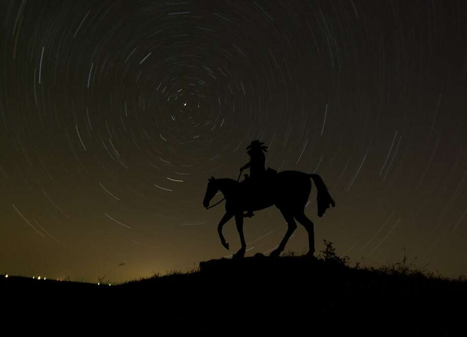 In this photo made using an hour-long time exposure, stars swirl behind a sign for a ranch near Olsburg, Kan. early Tuesday morning, Nov. 13, 2012. Photo: Charlie Riedel, Associated Press