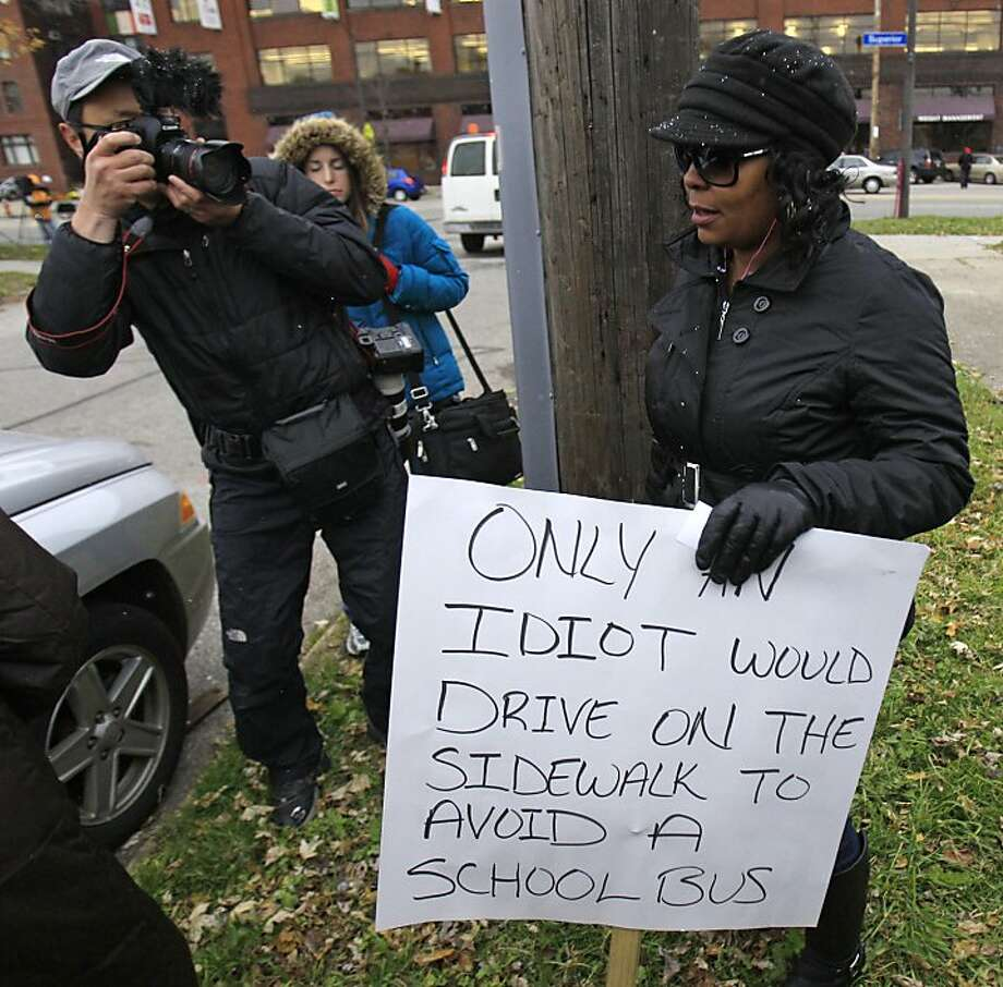 Shena Hardin walks back to her car after holding up a sign  to serve a highly public sentence Tuesday, Nov. 13, 2012, in Cleveland, for driving on a sidewalk to avoid a Cleveland school bus that was unloading children. A Cleveland Municipal Court judge ordered 32-year-old Hardin to serve the highly public sentence for one hour Tuesday and Wednesday. Photo: Tony Dejak, Associated Press