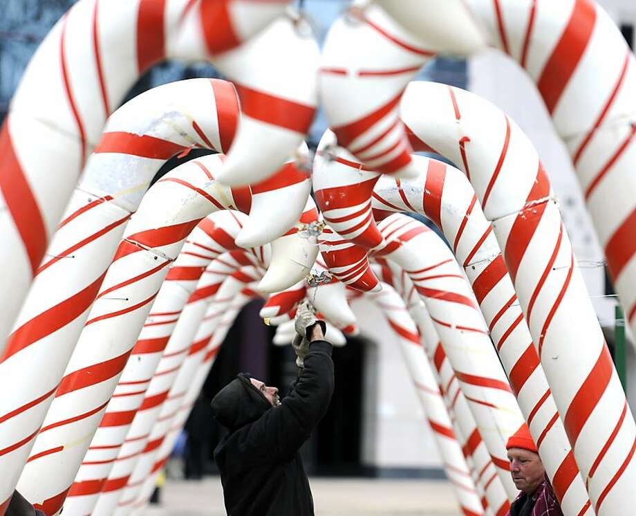 Dave Cooper wires the two ends of a pair of candy canes going up as Jeff Wolthais, right, helps as they set up Candy Cane Lane at Bronson Park on Tuesday afternoon, Nov. 13, 2012. Photo: Matt Gade, Associated Press