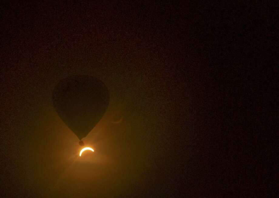 In this photo provided by Tourism Queensland, a hot air balloon floats in the air as a solar eclipse is observed near Cairns, in Queensland state, Australia, Wednesday, Nov. 14, 2012. Starting just after dawn, the eclipse cast its 150-kilometer (95-mile) shadow in Australia's Northern Territory, crossed the northeast tip of the country and was swooping east across the South Pacific, where no islands are in its direct path. (AP Photo/Tourism Queensland, David Barker) EDITORIAL USE ONLY Photo: David Barker, Associated Press