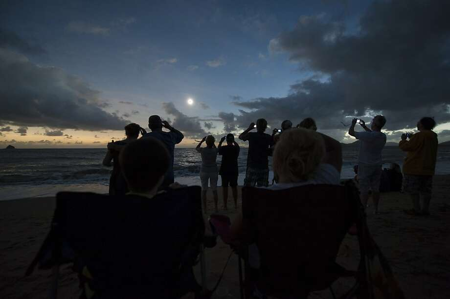 In this photo released by Tourism Queensland, people gather on Palm Cove beach in Queensland state, Australia, to watch a total solar eclipse Wednesday, Nov. 14, 2012. Starting just after dawn, the eclipse cast its 150-kilometer (95-mile) shadow in Australia's Northern Territory, crossed the northeast tip of the country and was swooping east across the South Pacific, where no islands are in its direct path. (AP Photo/Tourism Queensland, Murray Anderson-Clemence) EDITORIAL USE ONLY Photo: Murray Anderson-clemence, Associated Press