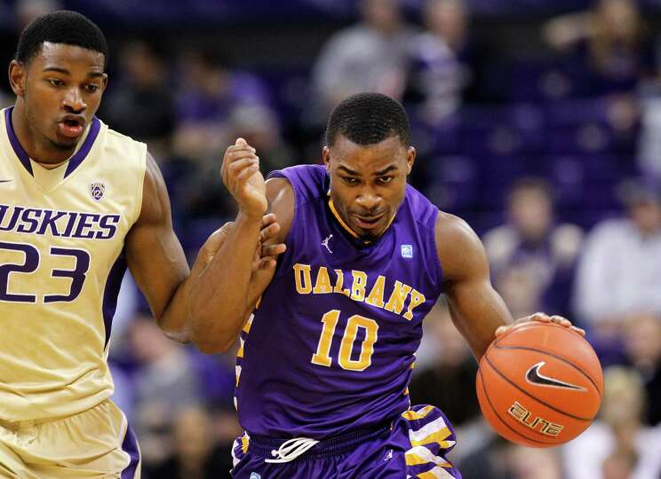 Washington's C.J. Wilcox (23) defends as Albany's Mike Black races up court in the first half of an