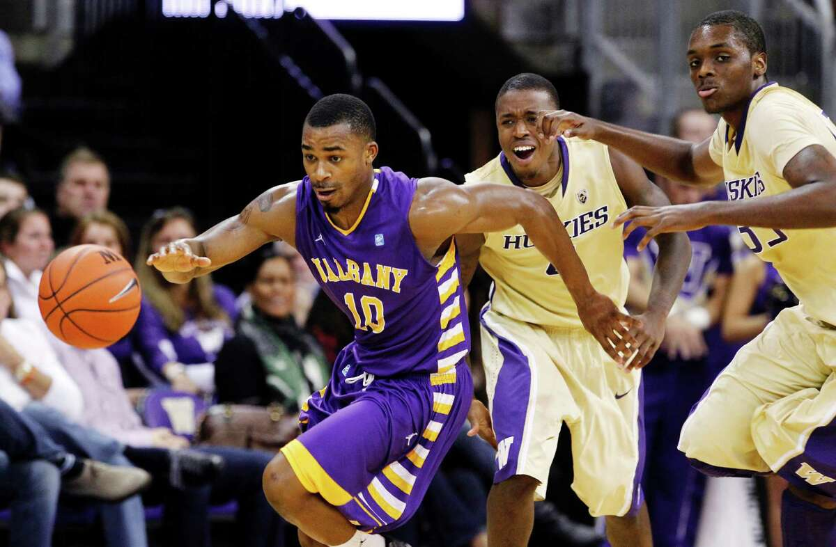 Albany's Mike Black (10) pushes the ball upcourt past Washington's Jernard Jarreau, right, and Hikeem Stewart in the second half of an NCAA college basketball game, Tuesday, Nov. 13, 2012, in Seattle. Black led all scorers with 22 points and Albany won 63-62.