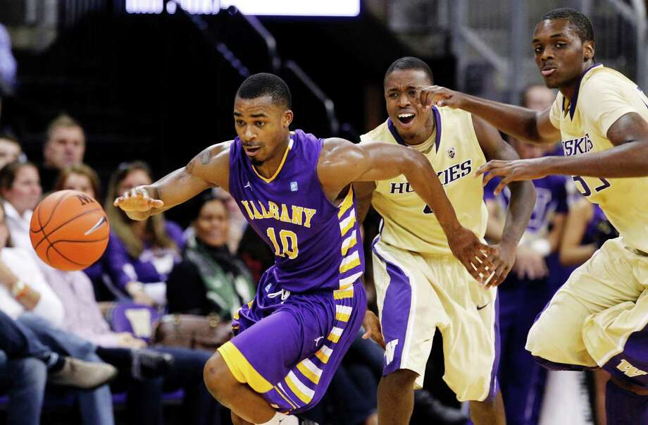 Albany's Mike Black (10) pushes the ball upcourt past Washington's Jernard Jarreau, right, and Hikeem Stewart in the second half of an NCAA college basketball game, Tuesday, Nov. 13, 2012, in Seattle. Black led all scorers with 22 points and Albany won 63-62. Photo: Elaine Thompson, AP / AP