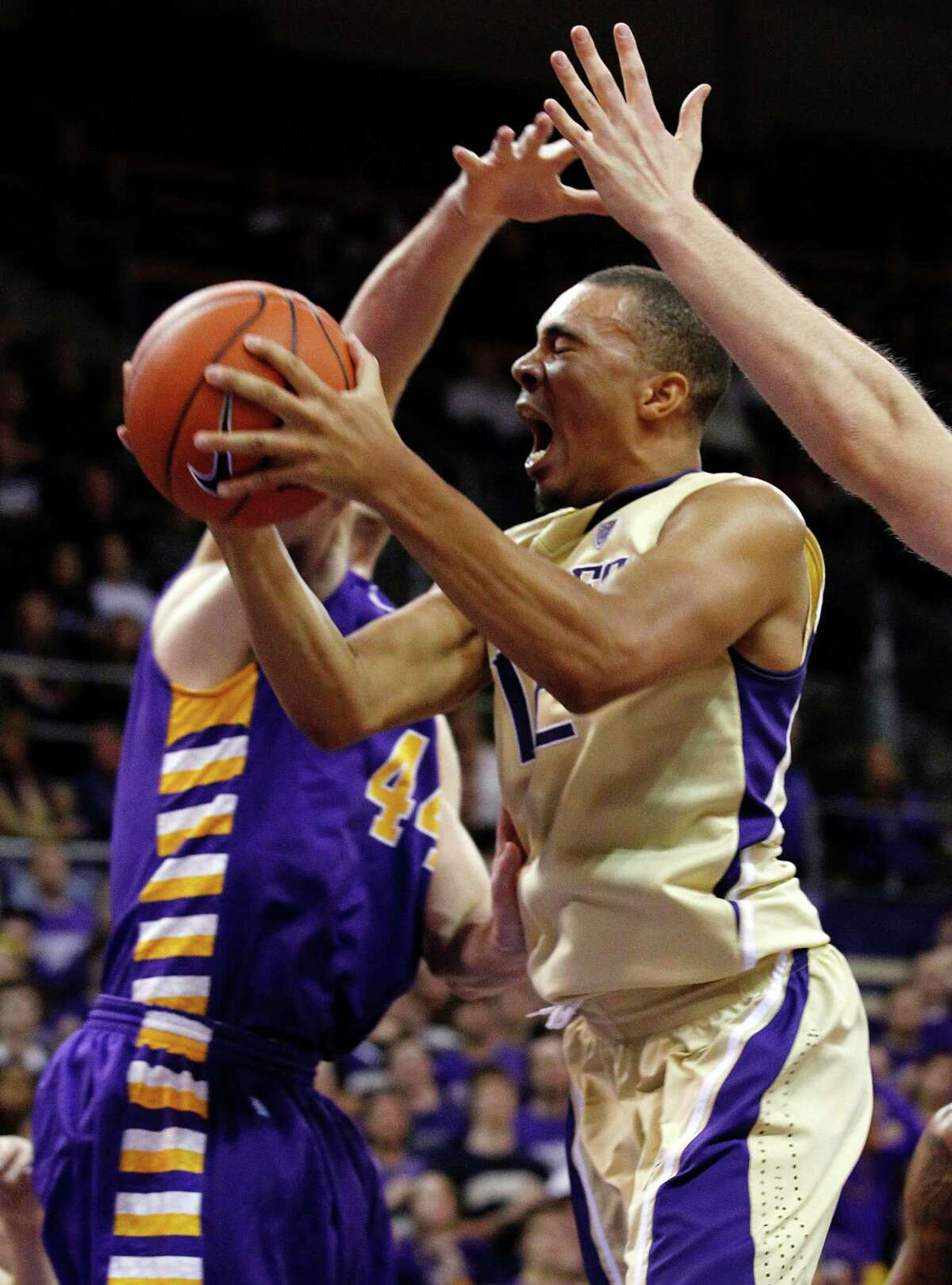 Washington's Andrew Andrews tries to drive between a pair of Albany defenders in the second half of an NCAA college basketball game, Tuesday, Nov. 13, 2012, in Seattle. Albany won 63-62.