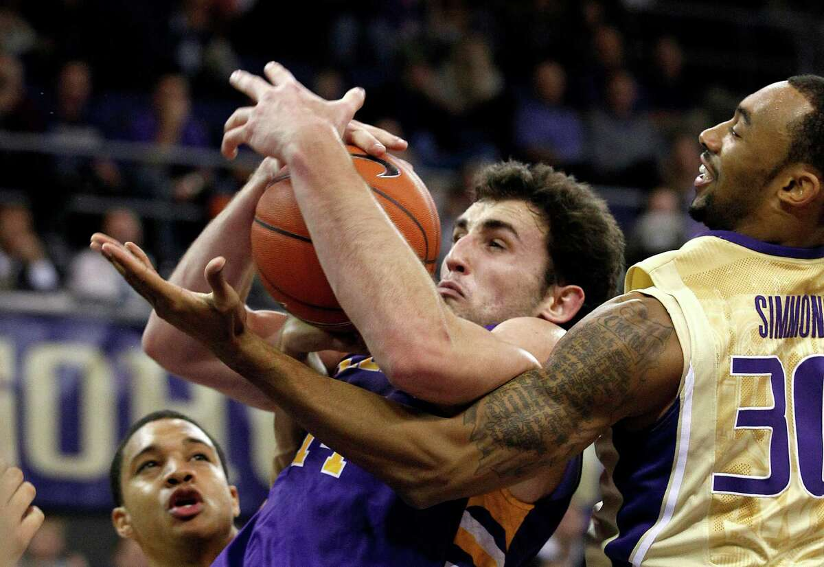Washington's Desmond Simmons, right, and Albany's Sam Rowley fight for the ball in the first half of an NCAA college basketball game, Tuesday, Nov. 13, 2012, in Seattle.