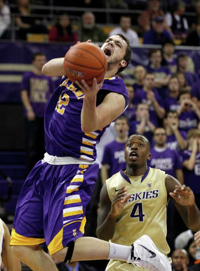 Albany's Peter Hooley shoots as Washington's Hikeem Stewart (4) trails in the first half of an NCAA college basketball game, Tuesday, Nov. 13, 2012, in Seattle. Photo: Elaine Thompson, AP / AP