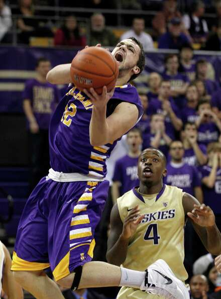 Albany's Peter Hooley shoots as Washington's Hikeem Stewart (4) trails in the first half of an NCAA