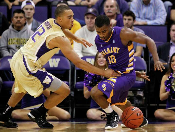 Washington's Andrew Andrews, left, defends Albany's Mike Black in the first half of an NCAA college