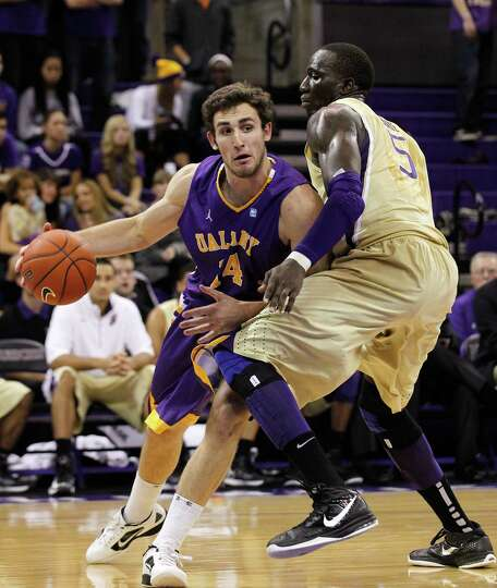 Washington's Aziz N'Diaye (5) defends as Albany's Sam Rowley drives in the first half of an NCAA col