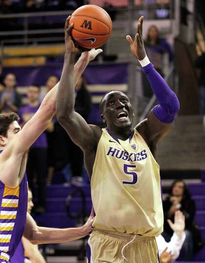 Washington's Aziz N'Diaye (5) shoots against the Albany defense in the first half of an NCAA college