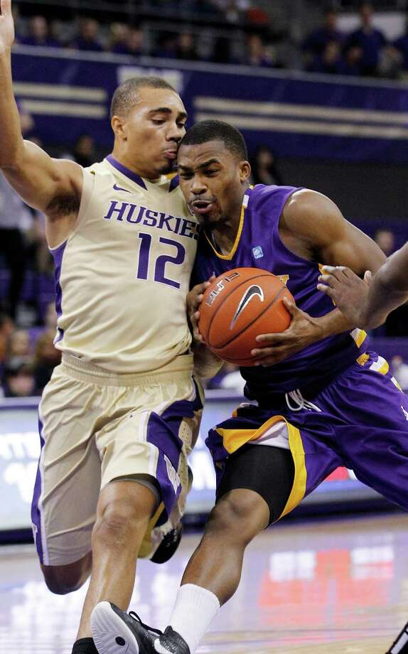 Washington's Andrew Andrews (12) collides with Albany's Mike Black in the first half of an NCAA college basketball game, Tuesday, Nov. 13, 2012, in Seattle. Photo: Elaine Thompson, AP / AP